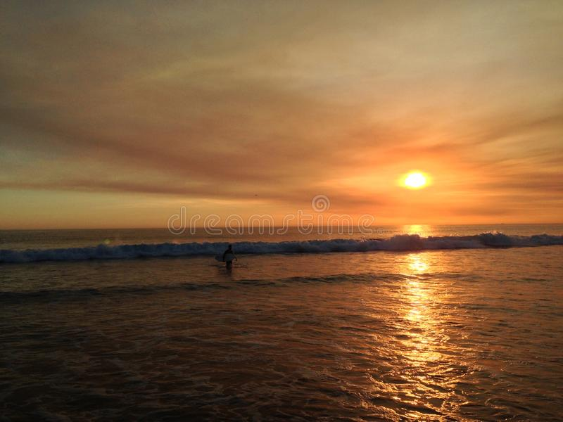 Pacific Ocean Sunset. Orange water reflection, orange clouds with surf wave and clouds royalty free stock photos