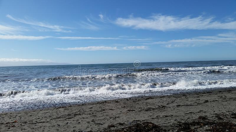 Sea shore in Alaska. Pacific ocean with surf and sand in Alaska with clouds and blue skies royalty free stock image