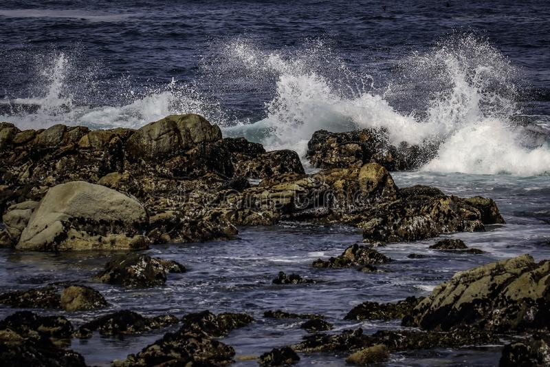 Rocky Seashore With Surf. Pacific Ocean textured rocks and blue water surf splash stock photography