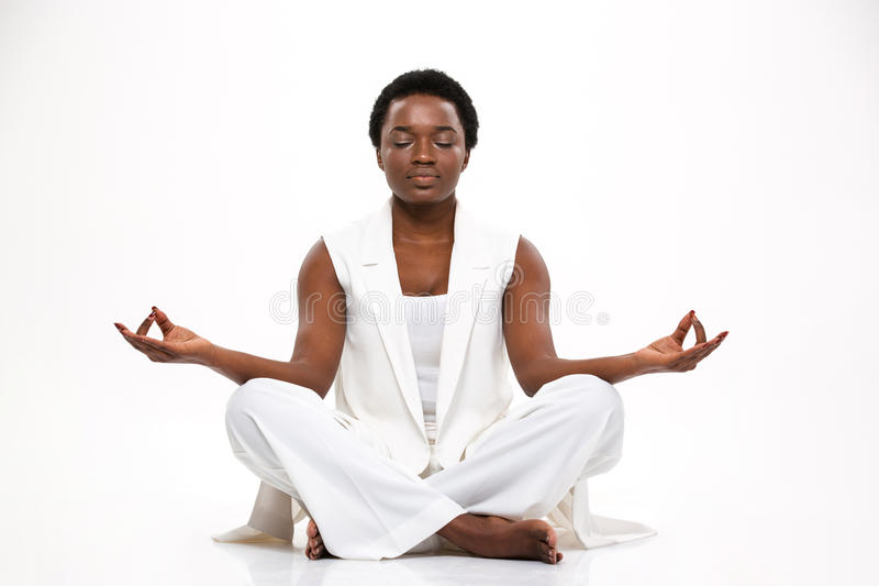 Pacified pretty african woman sitting and meditating in lotus pose stock photography