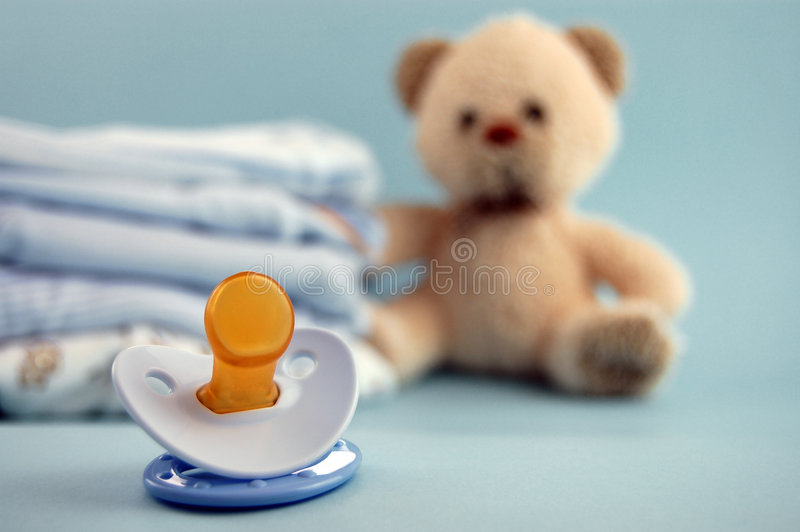 Pacifier and Baby Clothes stock photos