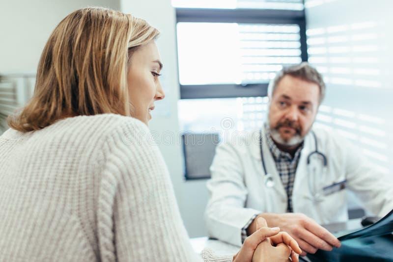 Pacjent opowiada z lekarką podczas konsultaci w klinice obraz stock