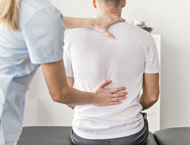 Pacjent przy fizjoterapią robi fizycznym ćwiczeniom z jego terapeuta fotografia stock