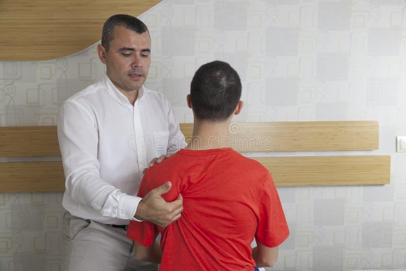 Pacjent robi niektóre dodatkowi specjalnemu ćwiczy pod nadzorem physic obraz stock