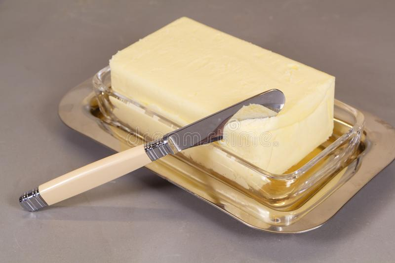 Pack of butter in a butter dish. Knife and pack of butter in a butter dish stock photo