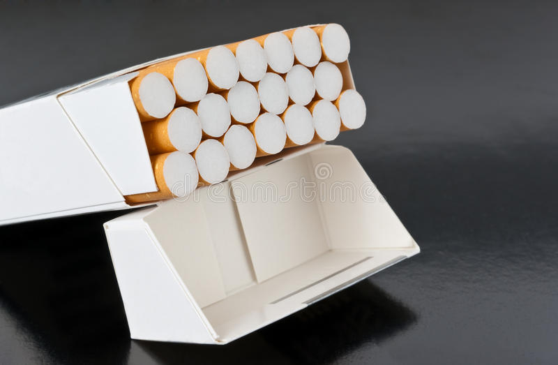 Pack of cigarettes. Open full pack of cigarettes over black royalty free stock image