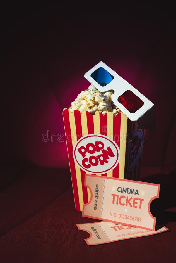 Cinema`s pop corn and 3d glasses on a cinema`s armchair royalty free stock images
