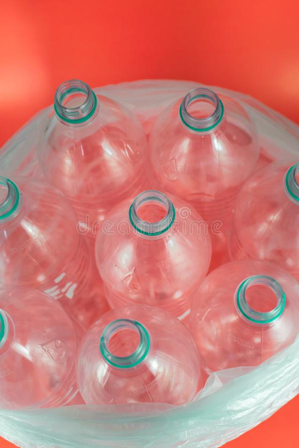 A pack of 8 empty and recyclable plastic water bottles, with no caps, blue seal, inside a plastic bag, on a salmon red stock images