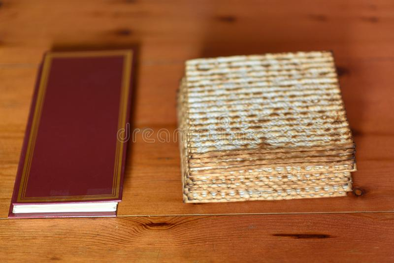 Passover. Traditional seder table set for a Jewish Festive meal matzah and Passover Haggadah. Pack of matzah or matzo or or matza and Passover Haggadah on a stock photography