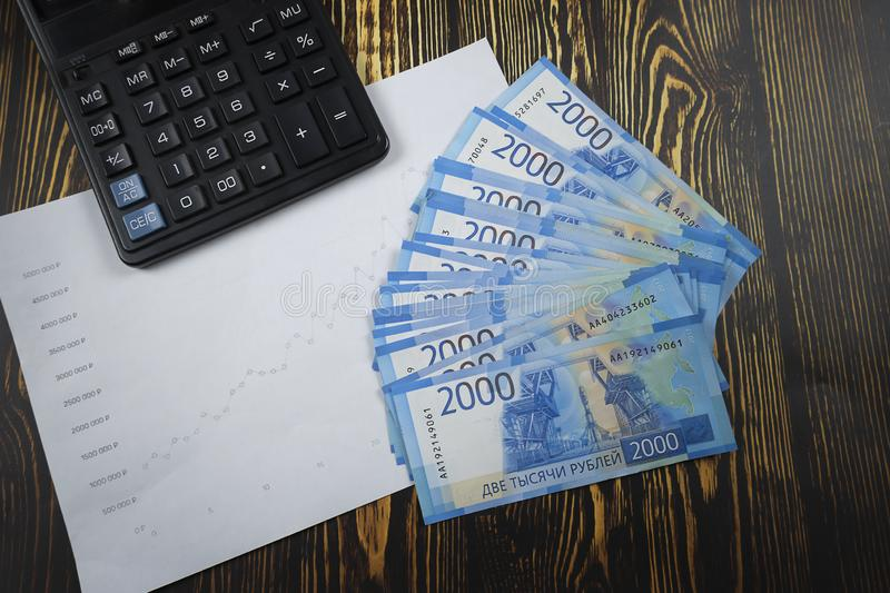 A pack of money two thousand Russians with a calculator and a graph of profitability stock photography