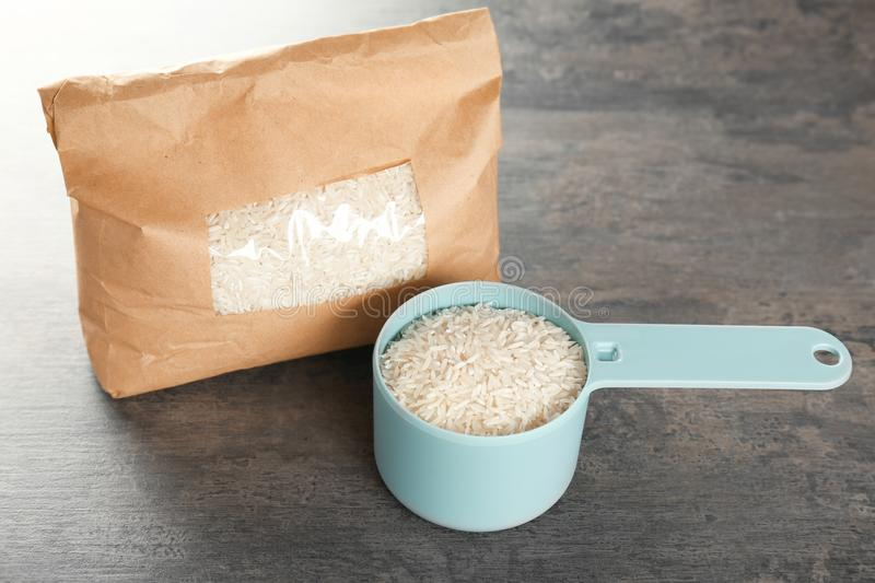 Pack of rice and full measuring scoop. On table stock images