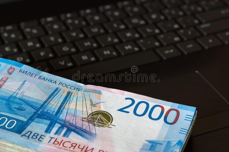 A pack of Russian rubles with a face value of 2000 rubles lies on the laptop keyboard. Top view. A pack of Russian rubles with a face value of 2000 rubles lies royalty free stock photos