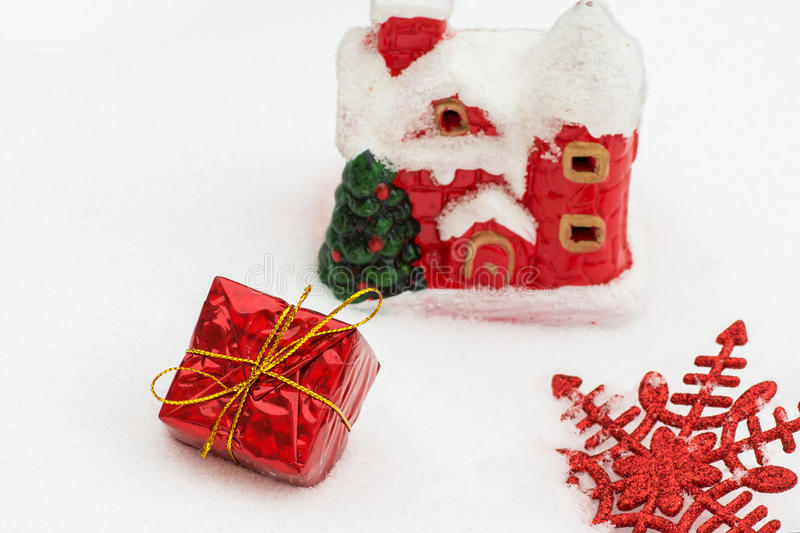 Packad julgåva av ett skinande rött pappers- hus för bakgrundsjultomten` s i snön, royaltyfria foton