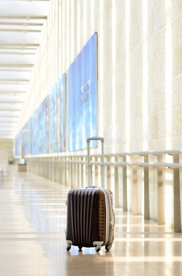 Packad loppresväska, flygplats Sommarferie och semesterbegrepp Handelsresandebagage, brunt bagage i tom korridor arkivbild
