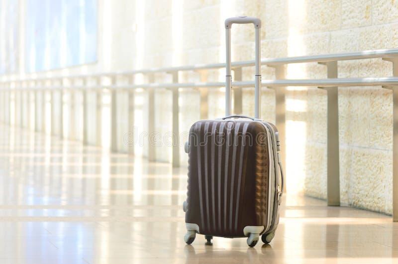 Packad loppresväska, flygplats Sommarferie och semesterbegrepp Handelsresandebagage, brunt bagage i tom korridor arkivfoto
