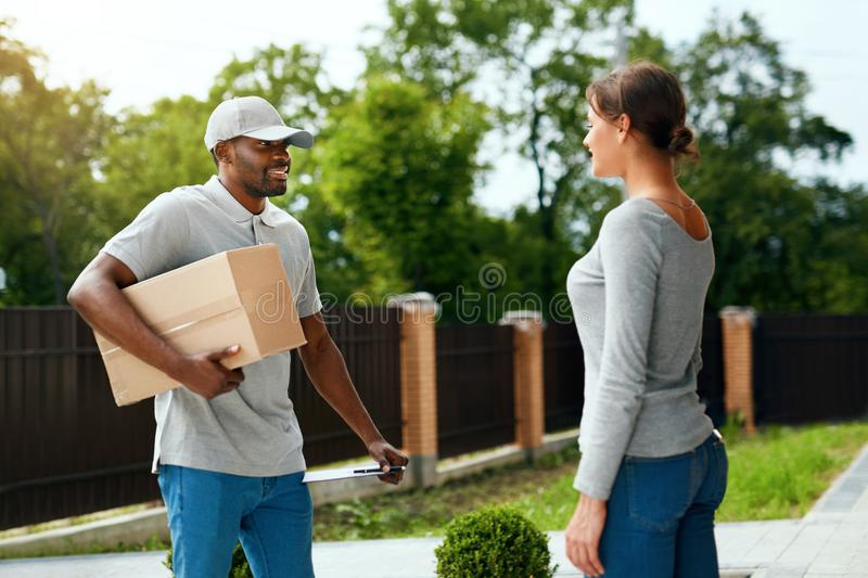 Package Delivering. Delivery Man Delivering Box To Woman. Outdoors. Courier Service. High Resolution royalty free stock photography