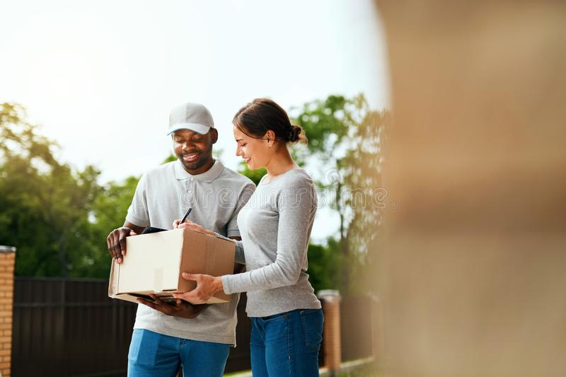 Package Delivering. Delivery Man Delivering Box To Woman. Outdoors. Courier Service. High Resolution stock photos