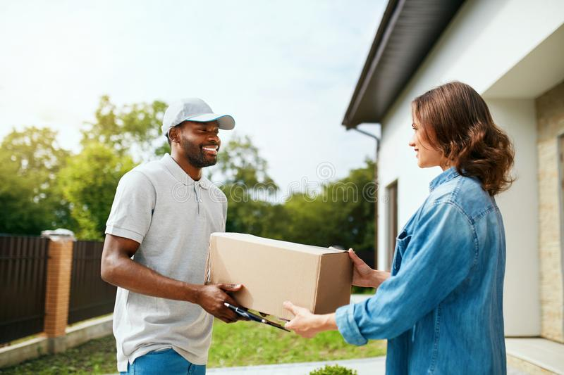 Package Delivering. Delivery Man Delivering Box To Woman. Outdoors. Courier Service. High Resolution stock photo