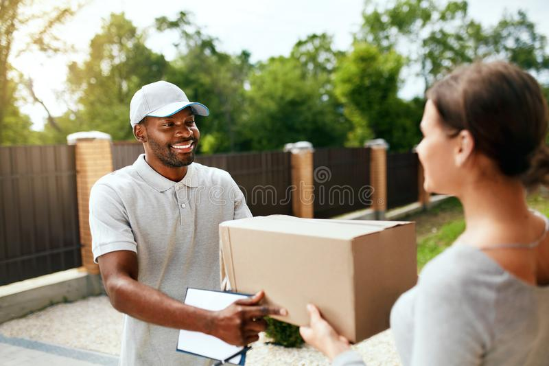 Package Delivering. Delivery Man Delivering Box To Woman. Outdoors. Courier Service. High Resolution royalty free stock images