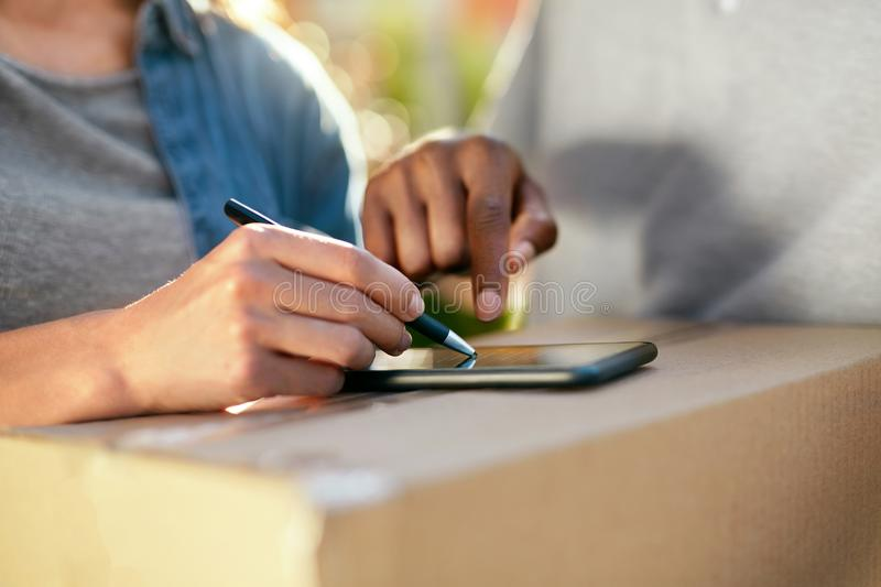 Package Delivery. Close Up Hand Signing On Phone On Box. Package Delivery. Closeup Of Female Hand Signing On Phone On Box, Receiving Package From Courier. High stock photography