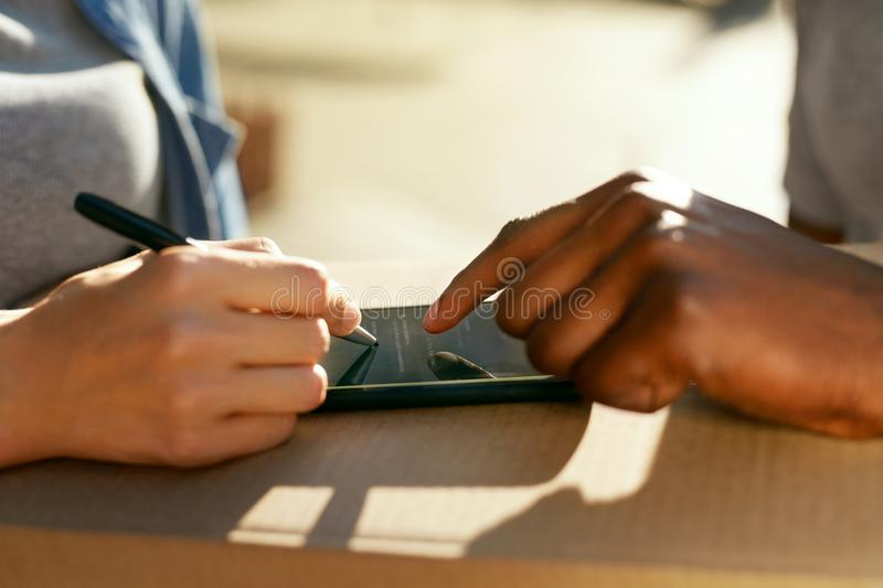 Package Delivery. Close Up Hand Signing On Phone On Box. Package Delivery. Closeup Of Female Hand Signing On Phone On Box, Receiving Package From Courier. High stock photo