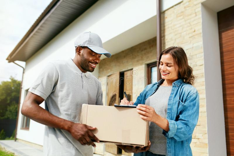 Package Delivery. Man Courier Delivering Box To Woman At Home. Female Receiving Parcel Outdoors, Signing Documents. High Resolution royalty free stock image