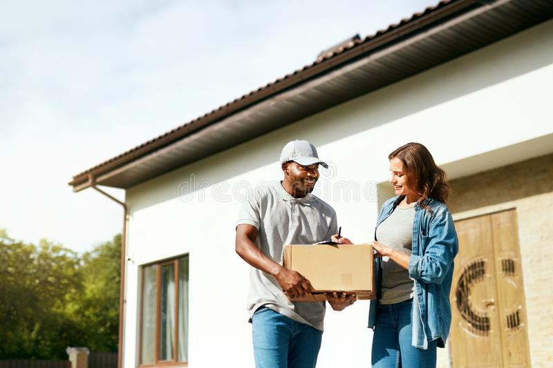 Package Delivery. Man Courier Delivering Box To Woman At Home. Female Receiving Parcel Outdoors, Signing Documents. High Resolution stock photography