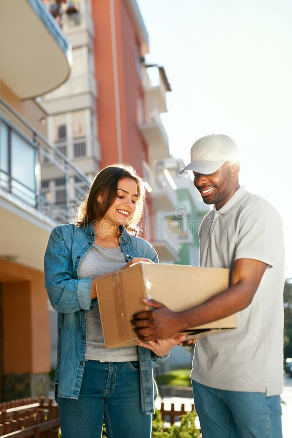 Package Delivery. Man Courier Delivering Box To Woman At Home. Female Receiving Parcel Outdoors, Signing Documents. High Resolution stock photo