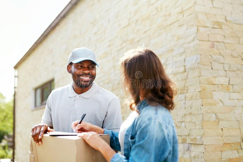Package Delivery. Man Courier Delivering Box To Woman At Home. Female Receiving Parcel Outdoors, Signing Documents. High Resolution royalty free stock photos