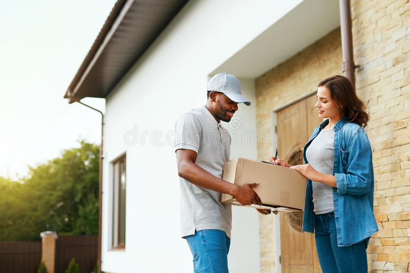 Package Delivery. Man Courier Delivering Box To Woman At Home. Female Receiving Parcel Outdoors, Signing Documents. High Resolution royalty free stock photography