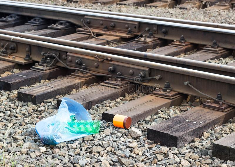A package with garbage on the railway thrown out from the window of the train by passengers, pollution, debris and the railway stock photography