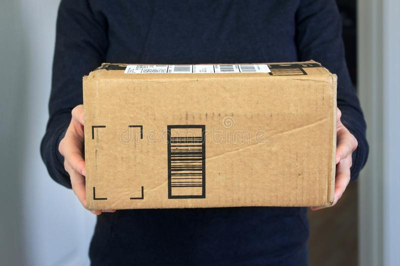 Package home delivery. A woman holding cardboard box package delivered at home stock photos