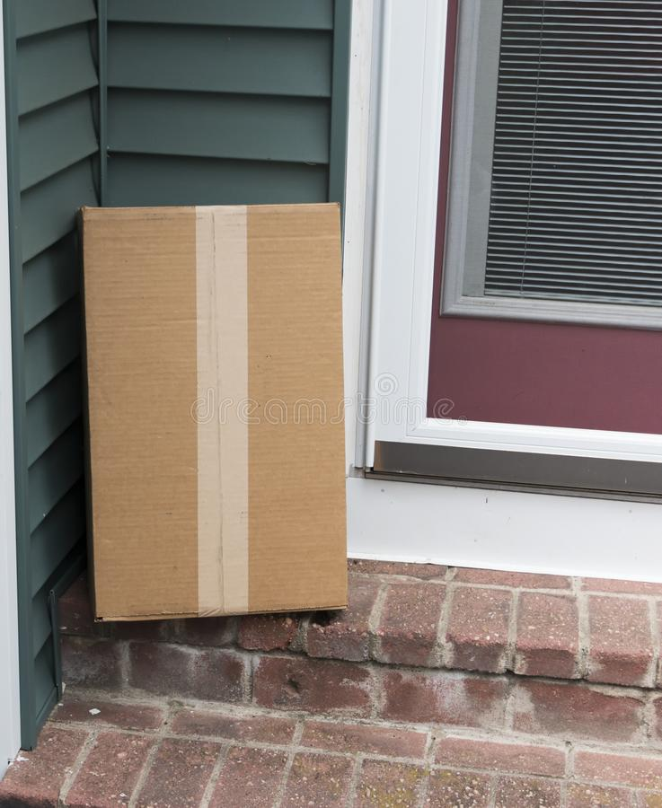 Package left on stoop of side door royalty free stock photography
