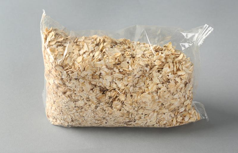 Package with raw oatmeal on light background stock photography