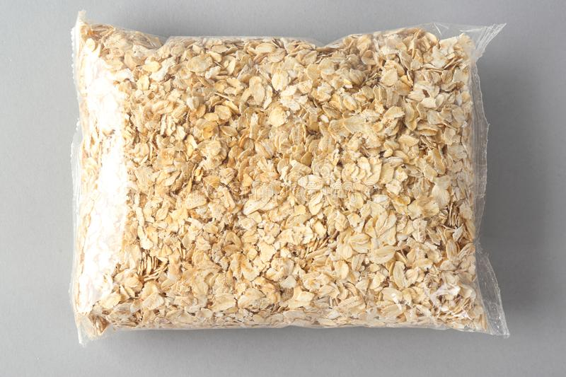 Package with raw oatmeal on light background stock photo