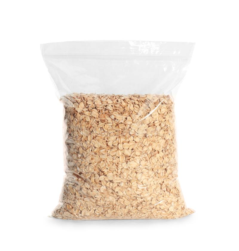 Package with raw oatmeal on white background stock images