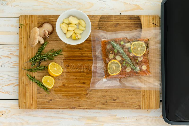 Packaged fish fillet sitting next to vacuum packer royalty free stock photo