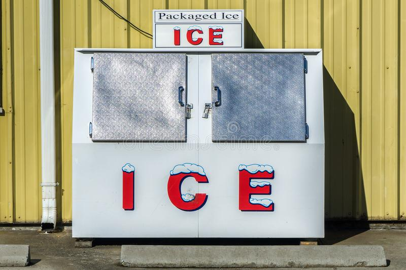 Packaged Ice freezer machine. Against a yellow wall during a hot and sunny day of summer outside a grocery store, Oregon, USA stock images