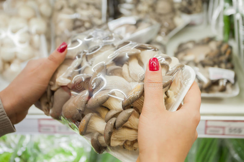 Packaged mushrooms with woman hand in the supermarket stock image