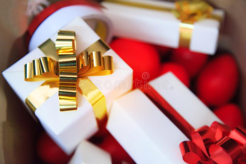 Packages and red hearts in brown bag present boxes with gold and red ribbons as holiday gift boxes for festive giving seasons. H stock photo