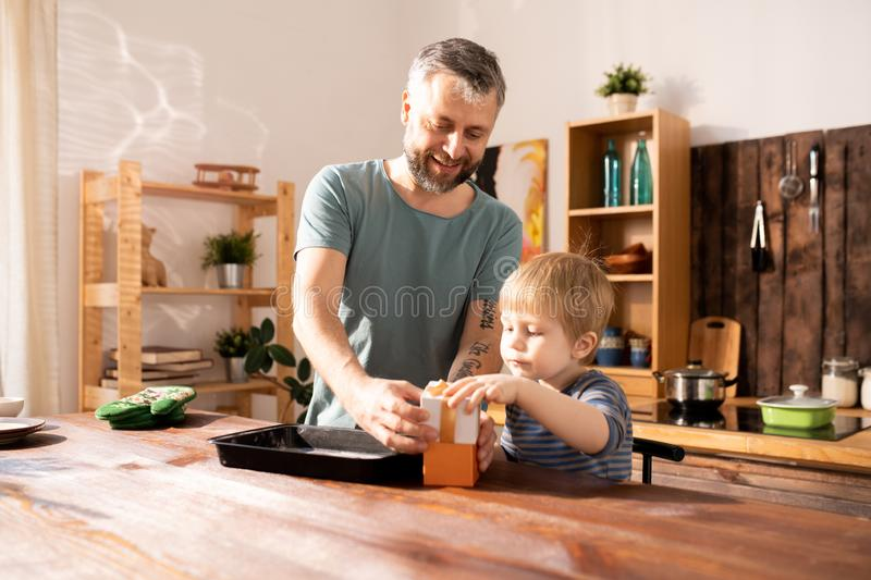 Packaging gift for mother. Cheerful father and son standing at wooden table and closing gift box while packaging gift for mother together royalty free stock photos