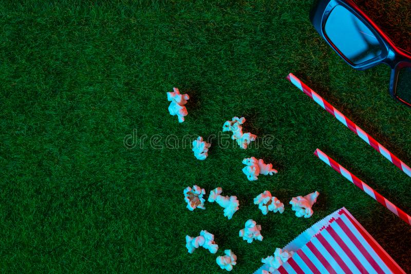 Packaging with popcorn straws for soda on a green lawn with 3D glasses for watching a movie. Creative light red-blue. Grass. Watching films about nature. In stock image