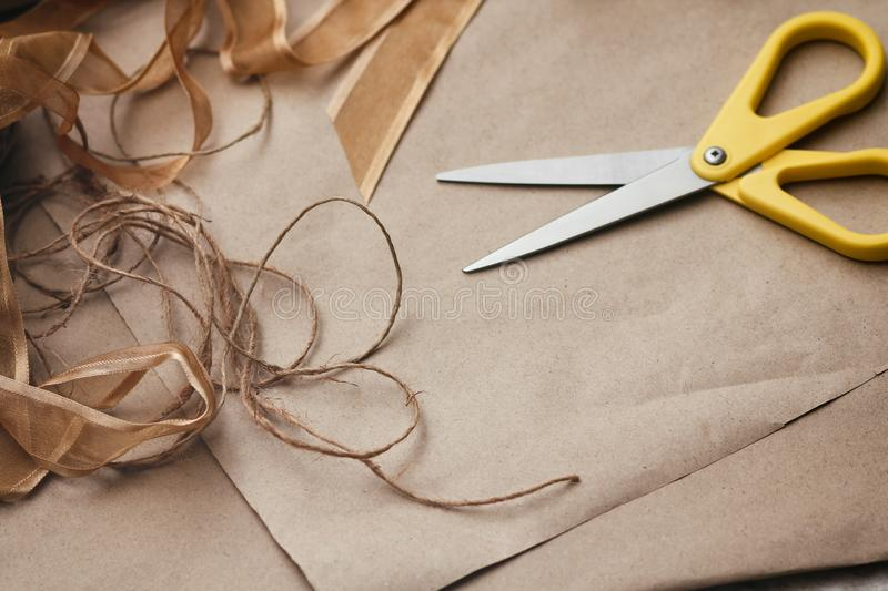 Packaging process. Presents wrapping. Yellow scissors, ribbons, hemp strings and threads, brown craft paper texture background. Gifts shop royalty free stock photos