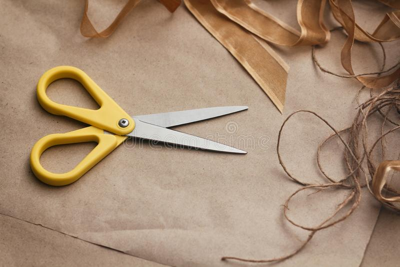 Packaging process. Presents wrapping. Yellow scissors, ribbons, hemp strings and threads, brown craft paper texture background. Gifts shop royalty free stock photo