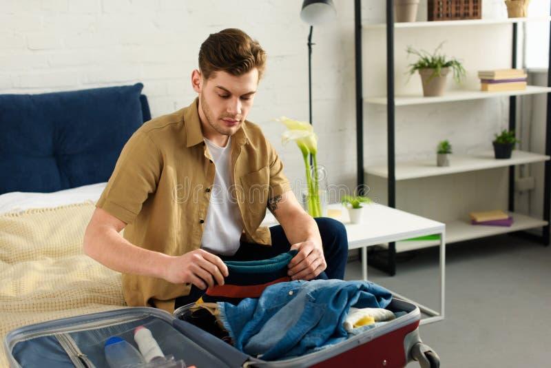 packande bagage för ung stilig man arkivbild