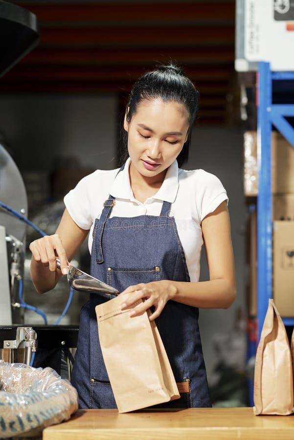 Packande kaffeb?nor f?r kvinna p? fabrik royaltyfria bilder