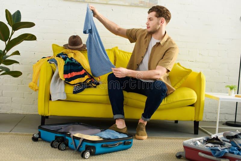 packande kläder för fundersam stilig man i lopppåsar arkivfoton