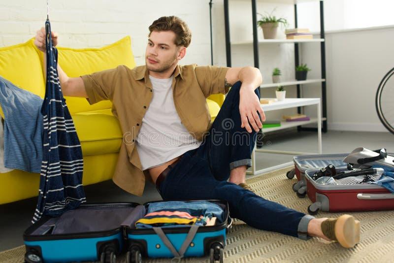 packande kläder för stilig man i resväskor royaltyfri foto