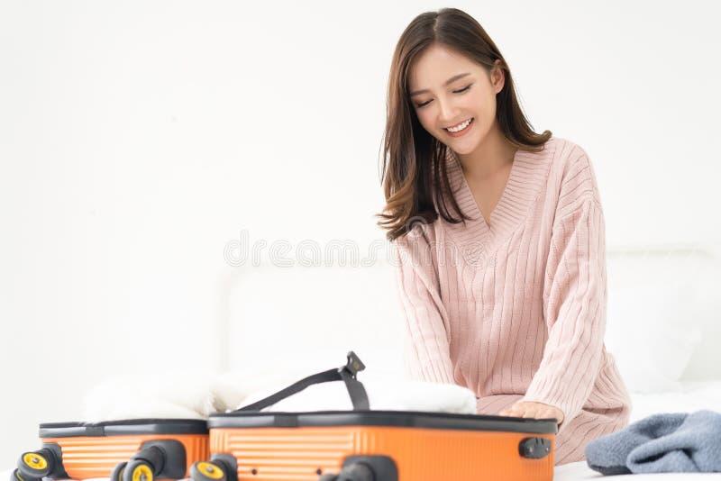 Packande kläder för ung härlig asiatisk kvinna in i resväskapåse på hennes säng för en semester Sommarsemester, lopp, turism och royaltyfri fotografi