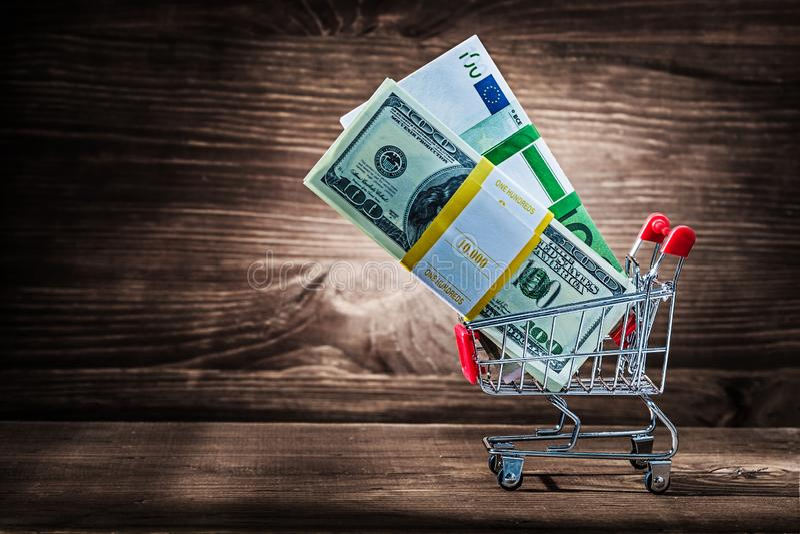 Packar av dollar och euro i shoppingvagn på tappningträ arkivfoto